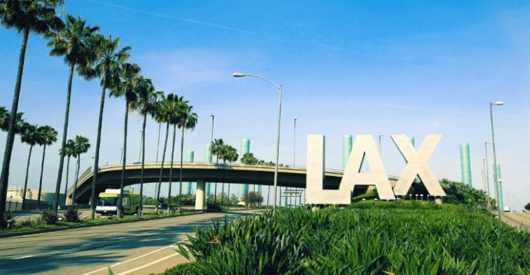 "Entrance to LAX airport with palm trees and an overpass behind the sign ""LAX."""