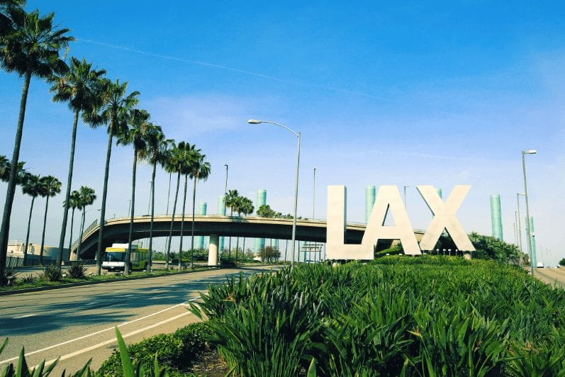 Entrance to LAX airport with palm trees and an overpass behind the sign
