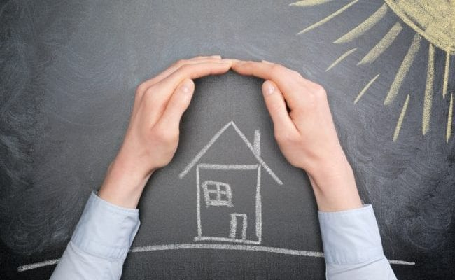 Hands around a house drawn on a chalkboard with a sun drawn in the corner of the chalkboard.