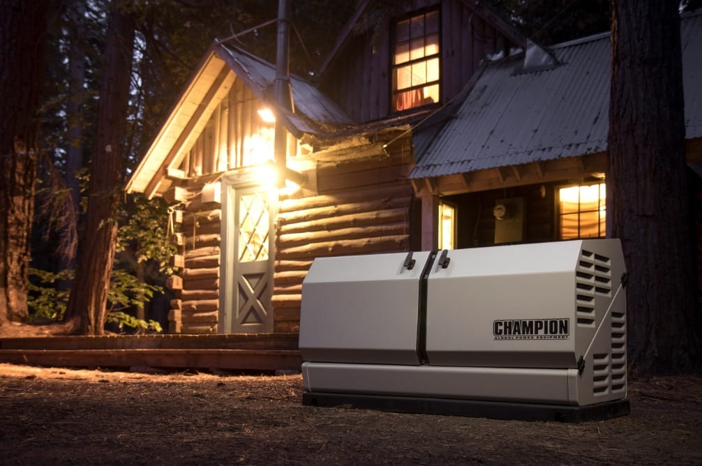 Champion home standby generator installed in front of a rural cabin at night.