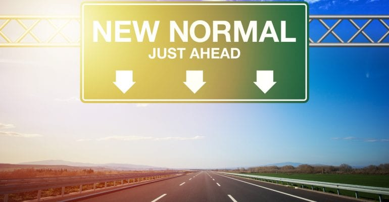 "Freeway sign on an empty highway saying ""New Normal Just Ahead."""