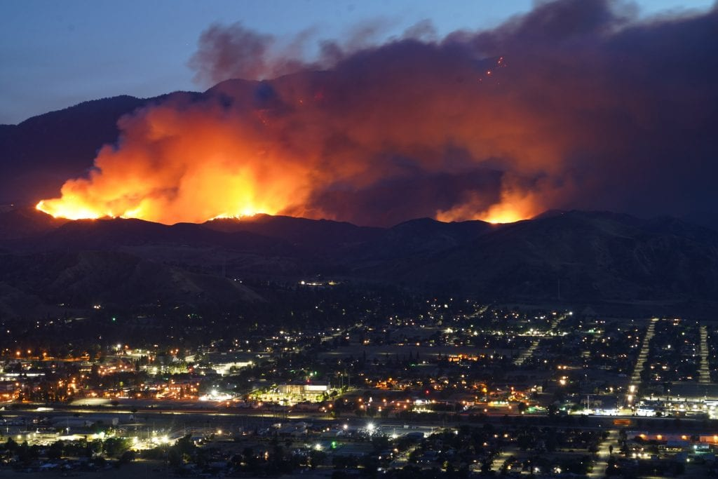 Massive wildfire in the foothills of a city at dusk.