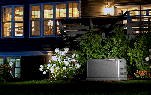 Home standby generator just outside of a home by greenery underneath a porch and windows.