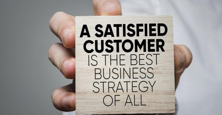 "Hand holding a wooden block that says ""A Satisfied Customer Is The Best Business Strategy of All."""