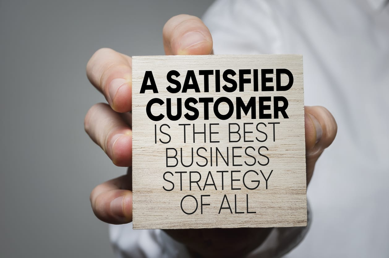 """Hand holding a wooden block that says """"A Satisfied Customer Is The Best Business Strategy of All."""""""