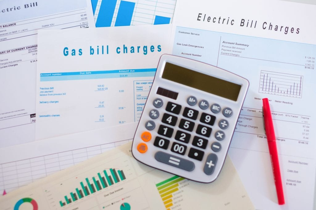 Desk calculator with invoices for energy and electric bills as elements of calculating a generator maintenance budget.