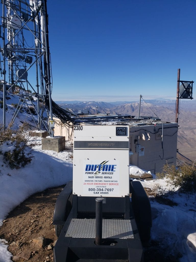 Duthie Power Services rental generator on a snowy mountaintop overlooking a valley.
