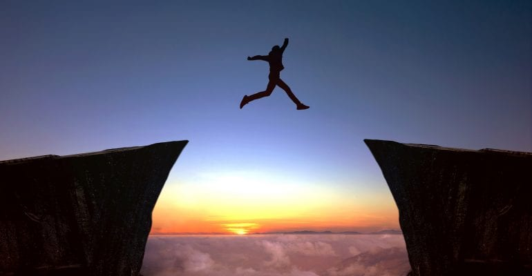 photo depicting the person who focuses on the target while leaping between two cliffs in silhouette against a sunset.