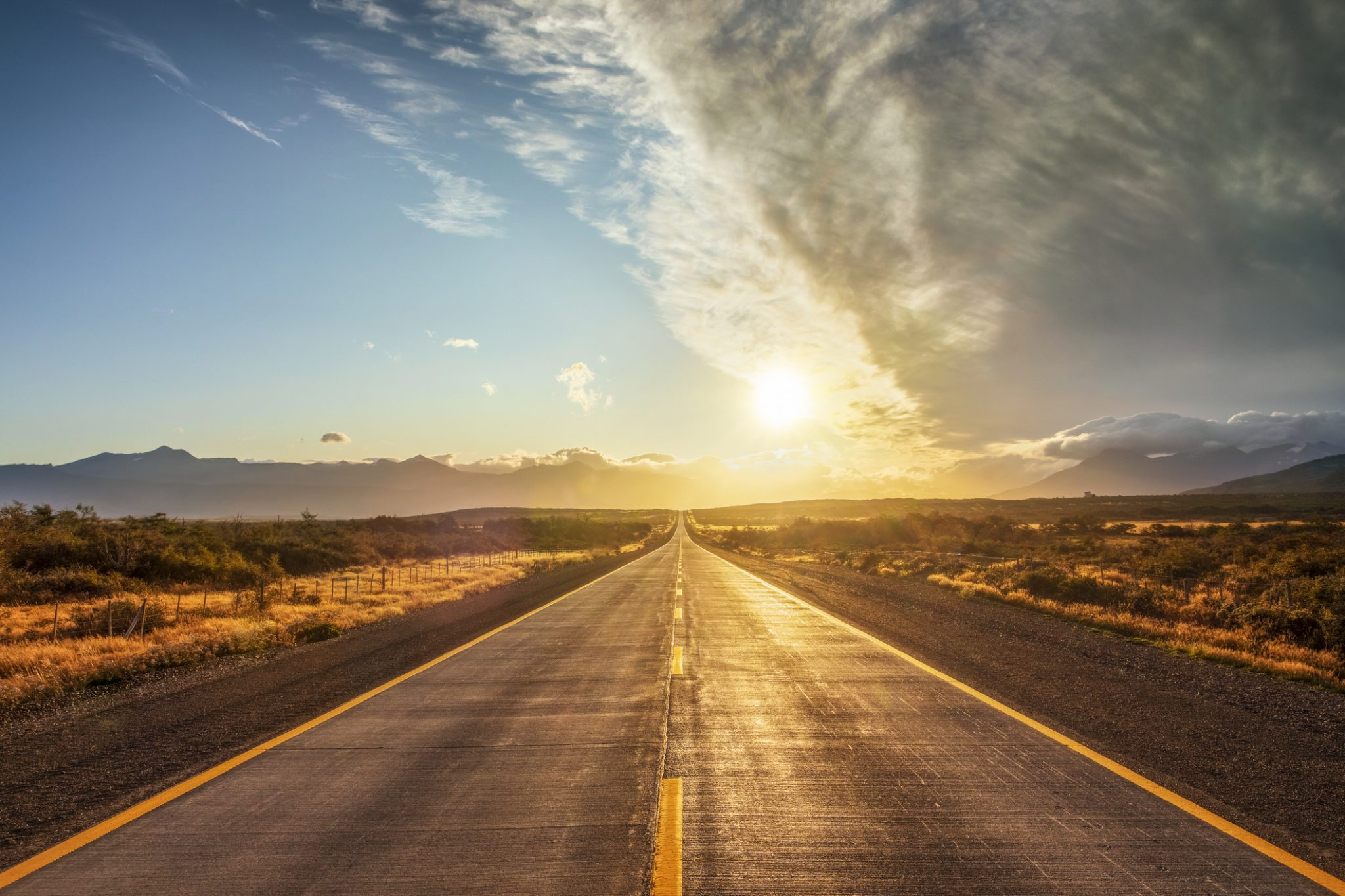 Sunset or sunrise at the end of an empty highway in the desert.