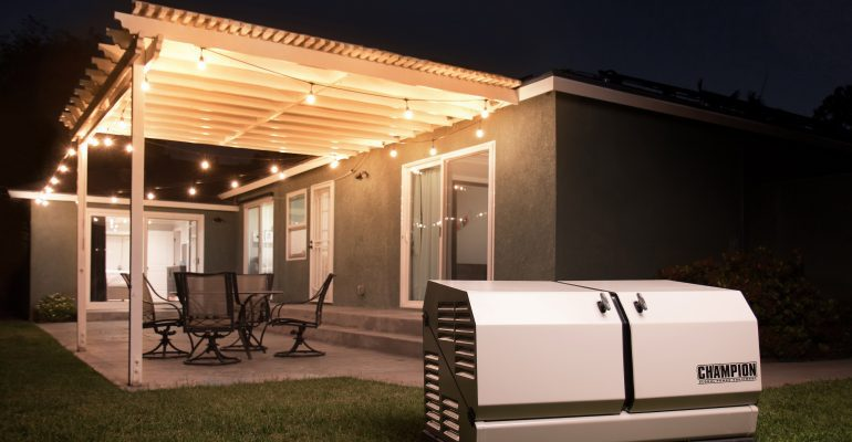 Champion home generator in the back yard of a home with a patio, patio furniture and outdoor lights.